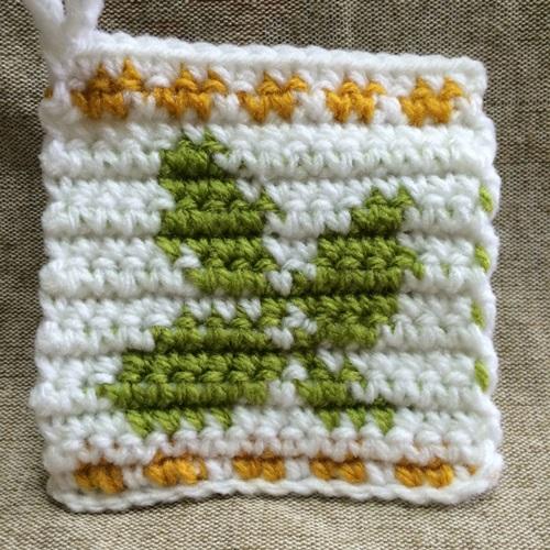 かぎ針編みの編み込み模様のアクリルたわし 北欧イメージの葉っぱ